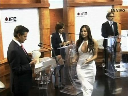 Former Playboy model and presidential debate assistant Julia Orayen (white) hands out cards to the four candidates during a televised debate at the Federal Electoral Institute in this handout still image taken from video, in Mexico City, May 7, 2012. Credit: Reuters/Instituto Federal Electoral/Handout/ via Reuters TV