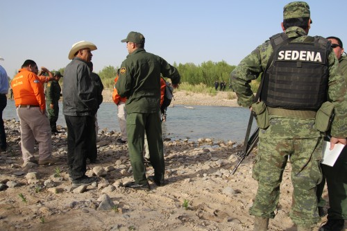 U.S. Border Patrol agents — their weapons left on the U.S. side of the Rio Grande — meet with the Mexican military in Boquillas, Mexico. (Photo by Lorne Matalon)