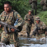 Armed Border Police cross tributary of Río Pirre on patrol looking for Colombian insurgents in Darién Province. (Lorne Matalon)