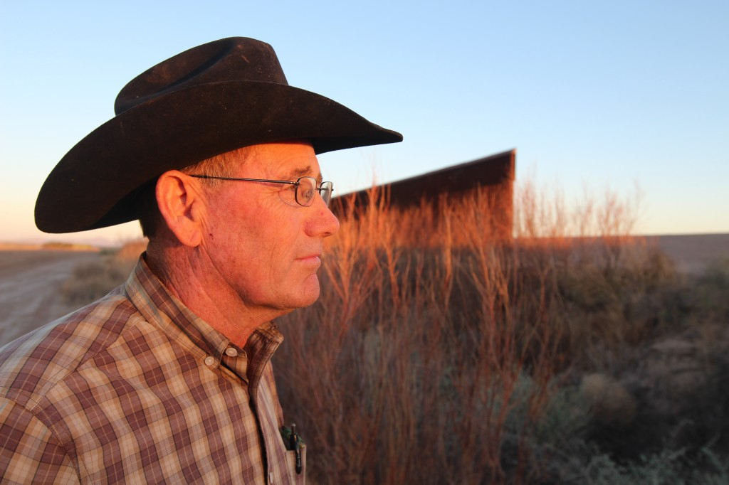 Alfalfa grower Craig Miller stands beside the border wall at Ft. Hancock, Texas. Miller says it's unfair to burden federal agents with new directives in rock-throwing scenarios.