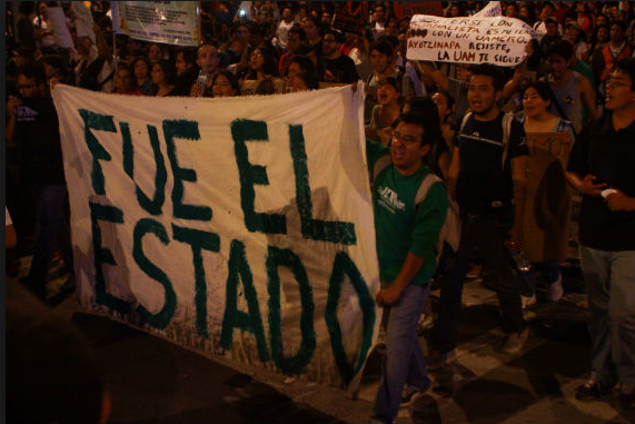 The banner reads 'fue el estado,' translated as 'It was the state.' There's no indication the murders of 43 students in Iguala, Guerrero went beyond the local level, but protesters say the alleged involvement of a mayor and police, both agents of the state imply that the Mexican state as an institution also bears some responsibility. (mioaxaca.com)