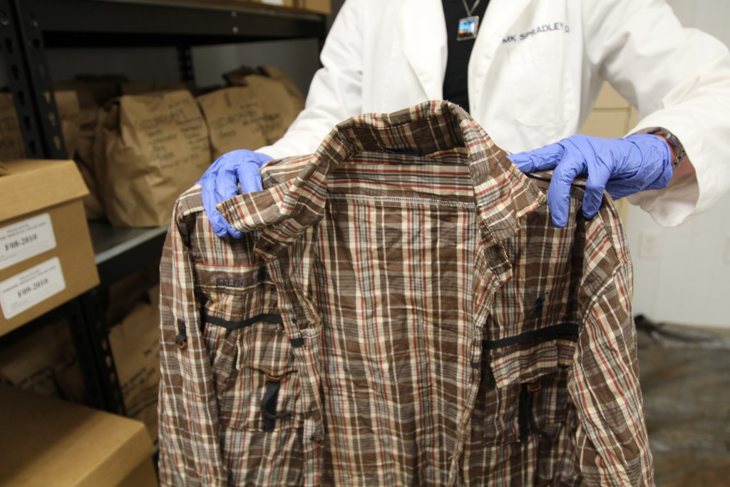 Forensic anthropologist Kate Spradley holds the shirt of a deceased Salvadoran migrant. The shirt's discovery set off a chain of events that ended with the successful but rare DNA confirmation of a migrant who perished in Texas after crossing the U.S.- Mexico border. (Lorne Matalon)