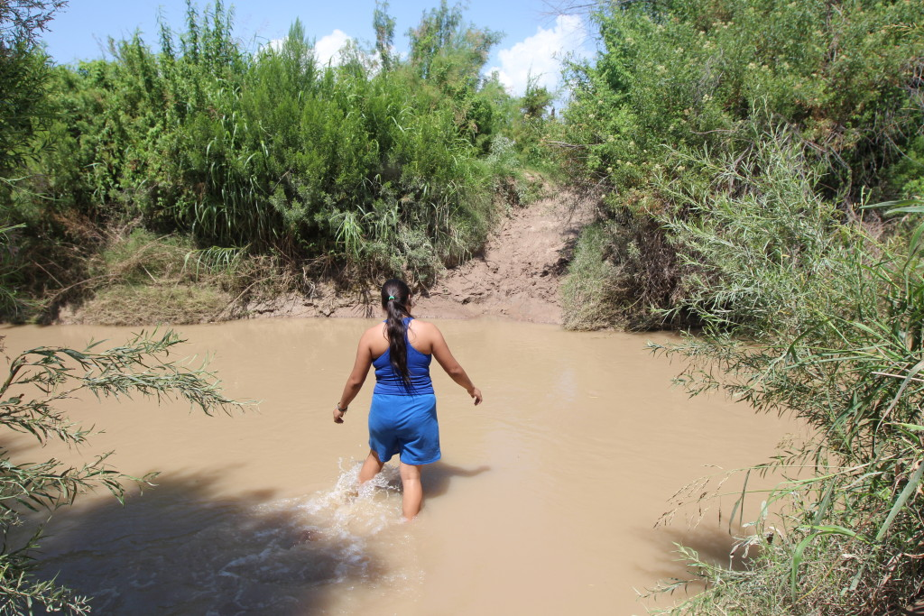 A woman wades across the Rio Grande into Chihuahua. She's a US citizen on her way to see family in Mexico living a few hundred yards from the shore. It's not illegal to exit the US here, only to return the same way. The nearest legal crossing is close to two hours away. (Lorne Matalon)