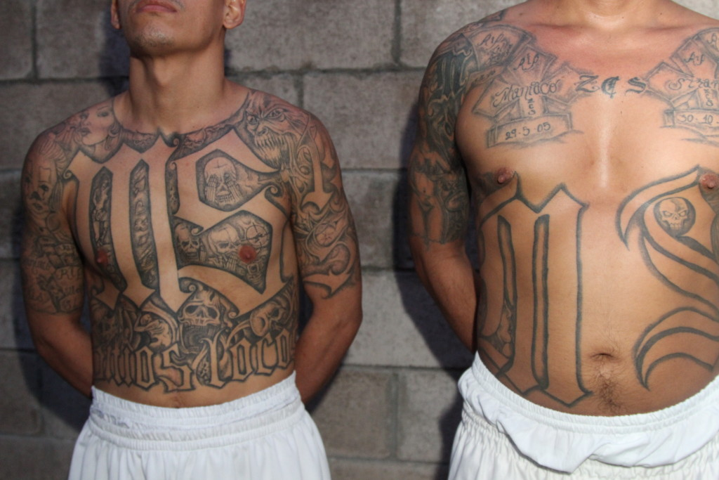 Two members of the Mara Salvatrucha gang (MS-13) stand in a prison in El Salvador. MS-13 was founded by Salvadoran immigrants in California in the 1980s. Recent intelligence gathered by US federal agents shared with the House Judiciary Committee in Washington, DC show that many Salvadorans cite gang violence as a prime motive for leaving Central America. (Lorne Matalon)