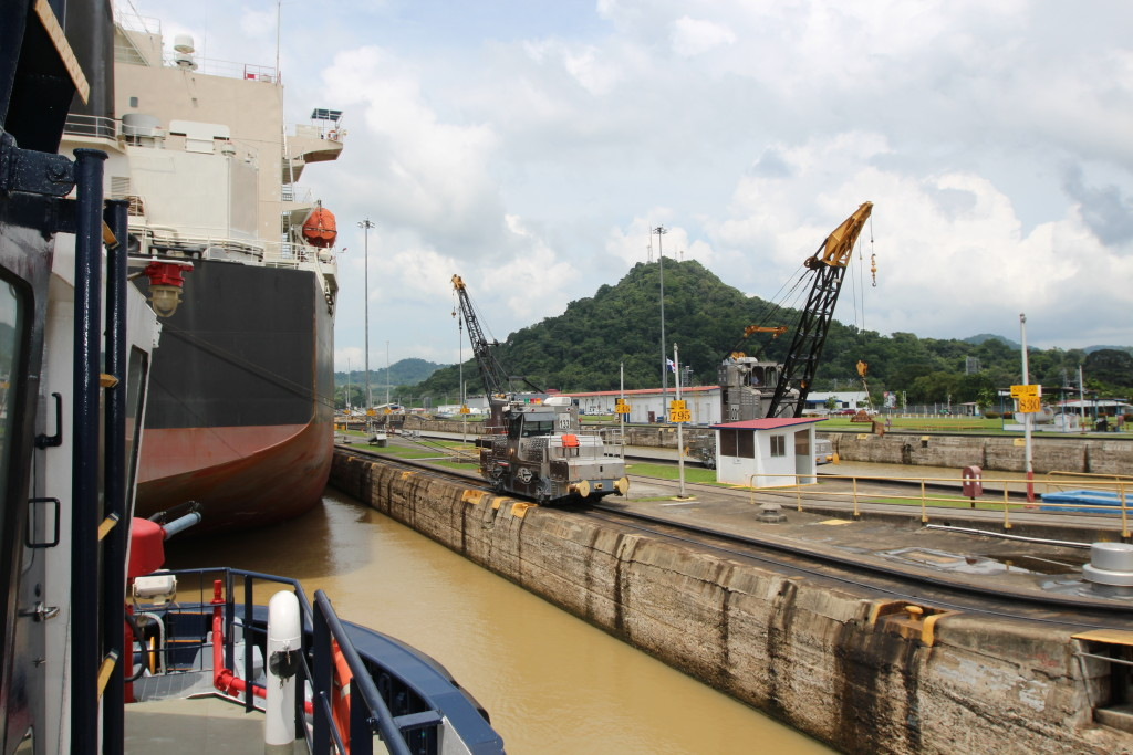 "There's very little room for vessel in front being guided through the Panama Cana's Pedro Miguel Locks. Rail cars equipped with cranes on the right are known as ""mules."" They keep the vessel moving forward while inside the lock chamber. (Lorne Matalon)"