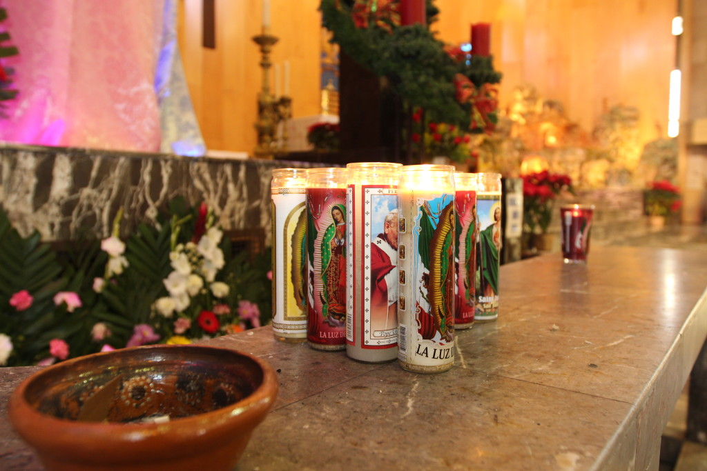 Visitors to the Cathedral of Our Lady of Guadalupe in Juárez place votive candles with the image of Virgen de Guadalupe, Mexico's patron saint, on a platform below the pulpit. Juárez residents interviewed for this story say the Pope's use of his position to promote social change resonates here. (Lorne Matalon)